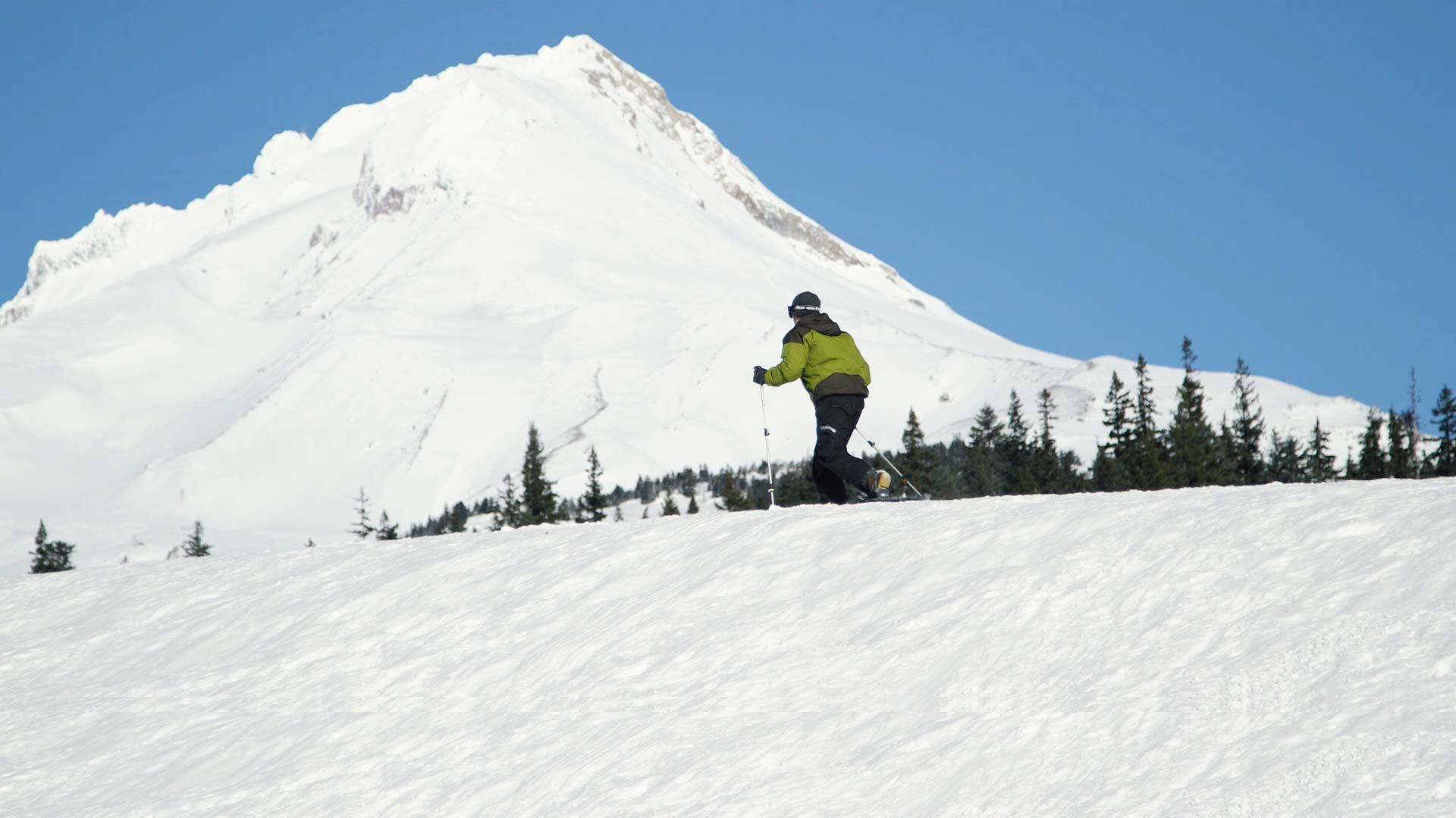 Still from Providence video of man snowshoeing past Mt. Hood