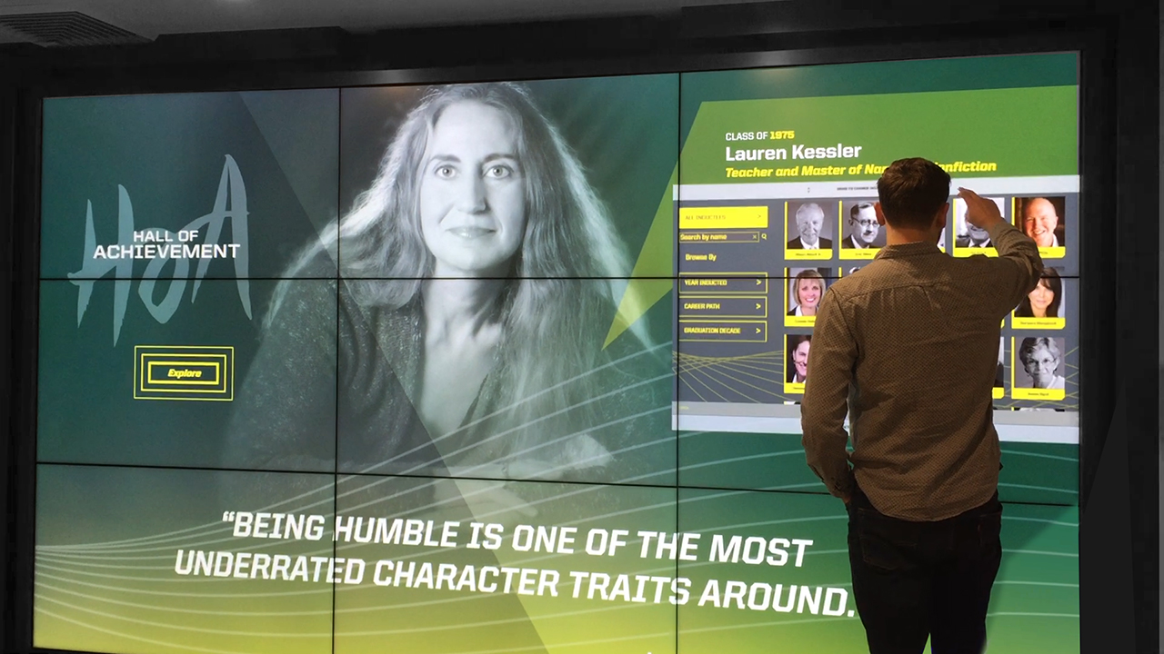 Person interacting with Hall of Achievement video wall