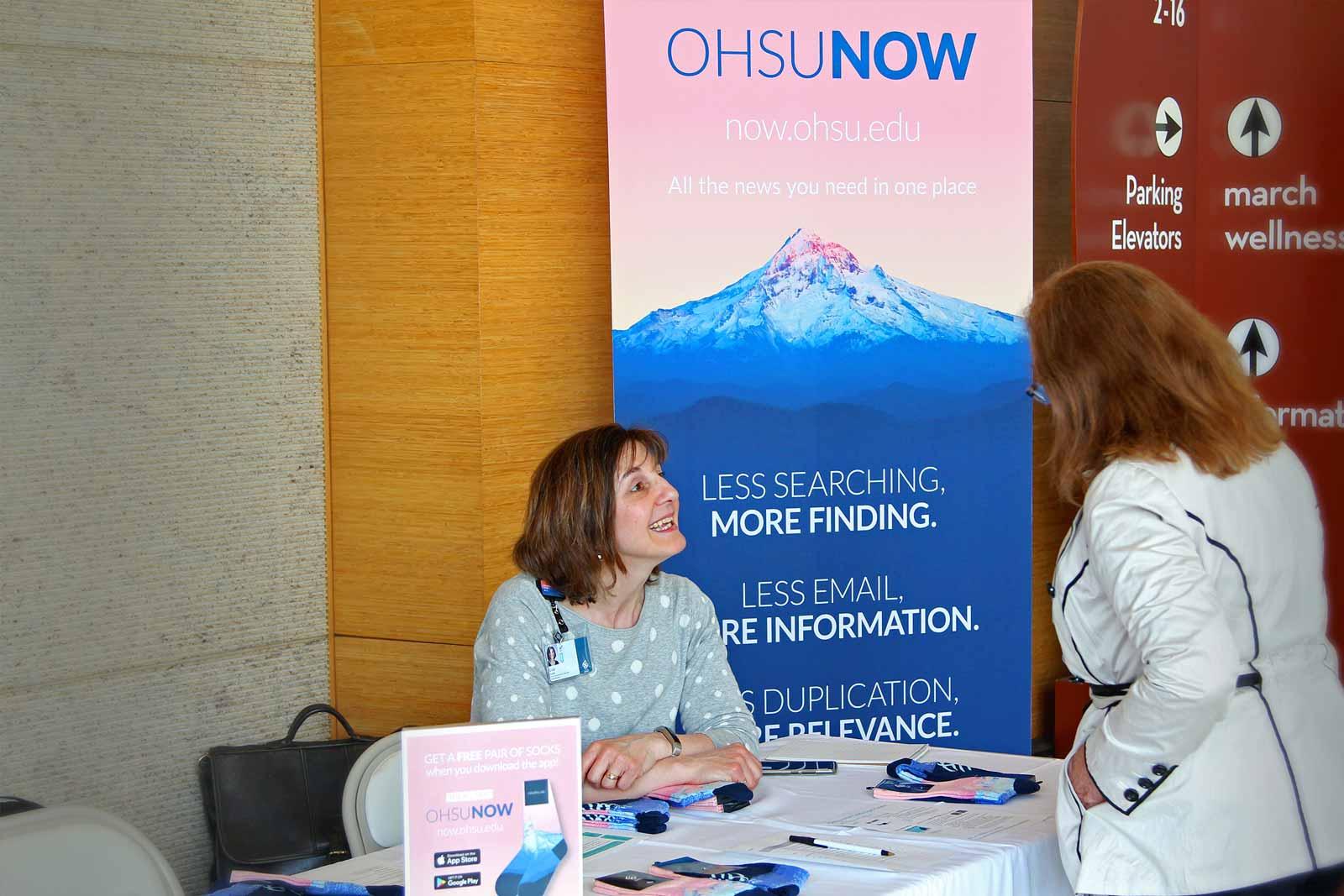 Photo of OHSU employee greeting employees providing OHSU Now branded socks